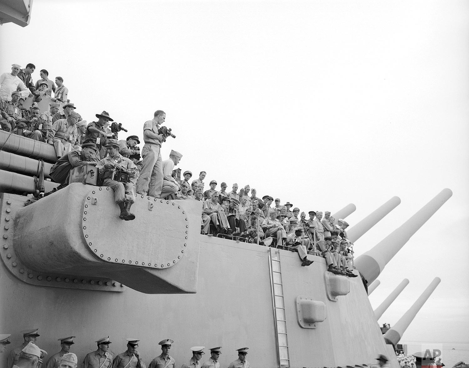 """Spectators and photographers use 16"""" gun turret in Japan, as vantage point on the USS Missouri. (AP Photo/Max Desfor)"""