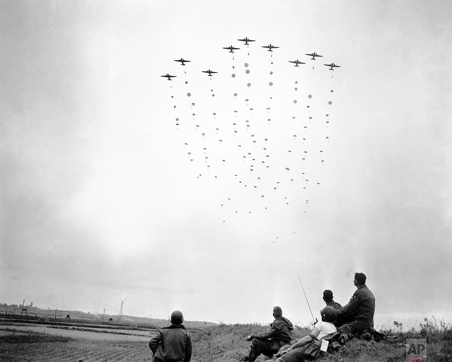 U.S. paratroopers leave their planes in a mass drop behind enemy lines in the Sunchon area of North Korea on Oct. 25, 1950 during an operation designed to block the escape route of the retreating Chinese and to attempt to rescue American prisoners. Members of an advance party (foreground) watch the landing. (AP Photo/Max Desfor)