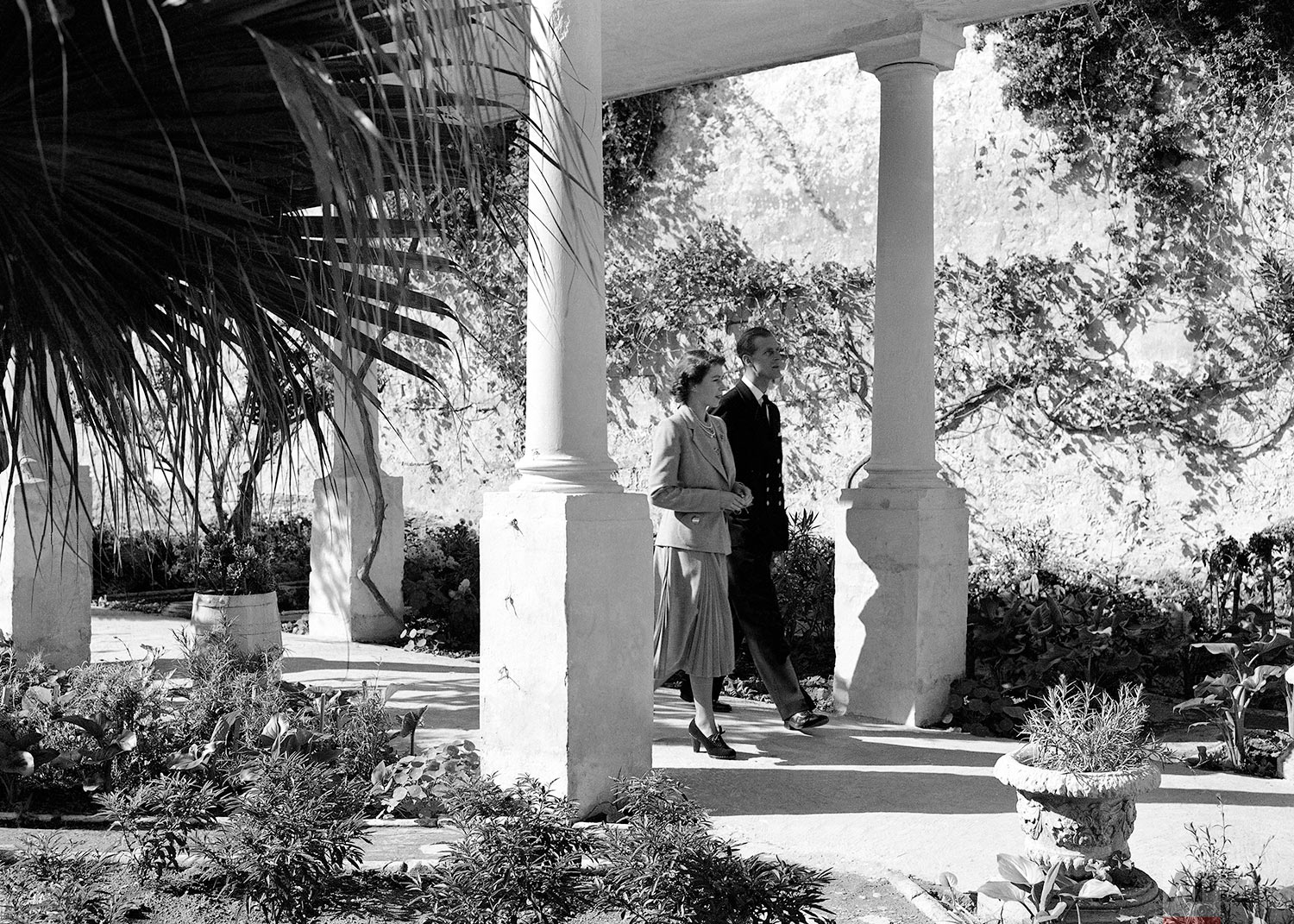 """Princess Elizabeth and her husband, Philip, Duke of Edinburgh, are seen strolling in the gardens of the Villa Guardamangia, Malta on Nov. 23, 1949. The Princess is residing at the Villa during her stay in the island to visit her husband. The Duke of Edinburgh is First Lieutenant aboard the destroyer """"Chequers"""" presently refitting at Malta. (AP Photo/Max Desfor)"""
