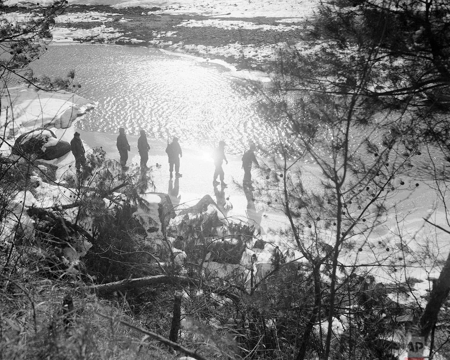 Cold winter sun creates a deceptively peaceful scene as it silhouettes an early morning patrol setting out over the Icy shore of a Korean stream in the Wonju area on Jan. 25, 1951. Allied patrols probing north of Wonju were finding little evidence of enemy concentrations. (AP Photo/Max Desfor)