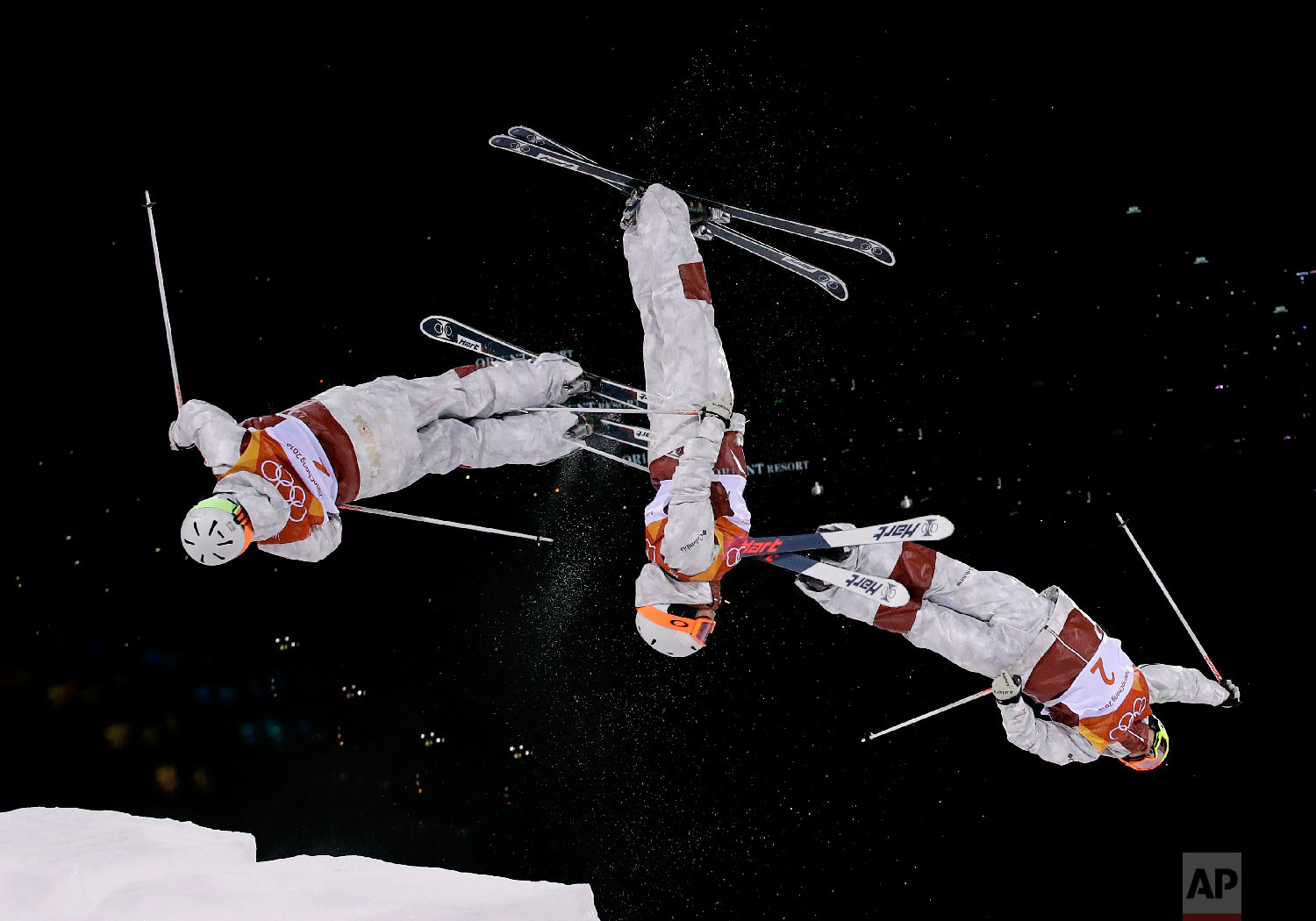 In this multiple exposure photo, AndiNaude, of Canada, jumps during the women's moguls finals at Phoenix Snow Park at the 2018 Winter Olympics in Pyeongchang, South Korea, Sunday, Feb. 11, 2018. (AP Photo/Gregory Bull)