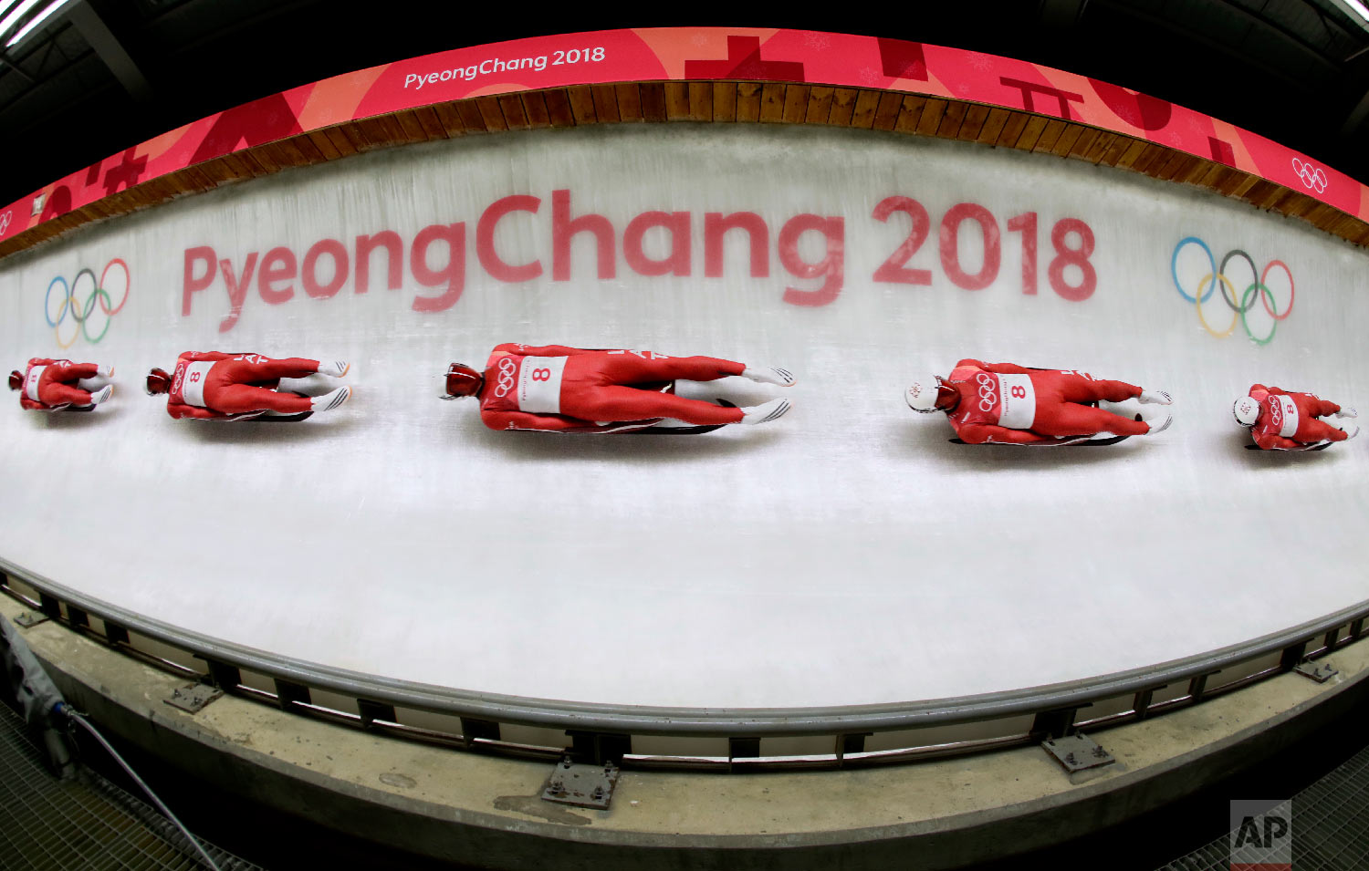 In this multiple exposure photo, Kristers Aparjods, of Latvia, makes his third run during final heats of the men's luge competition the 2018 Winter Olympics in Pyeongchang, South Korea, Sunday, Feb. 11, 2018. (AP Photo/Charlie Riedel)