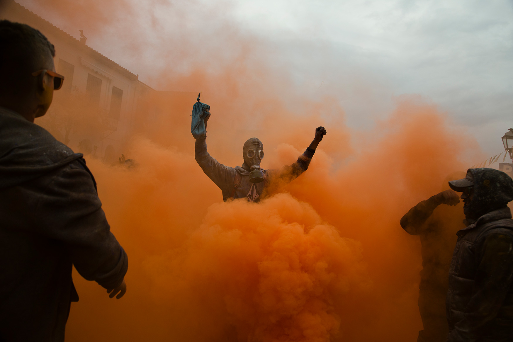 in this Monday, Feb. 19, 2018 photo, revelers take part in the flour war, a unique colorful flour fight marking the end of the carnival season in the port town of Galaxidi, some 200 kilometers (120 miles) west of Athens.  (AP Photo/Petros Giannakouris)