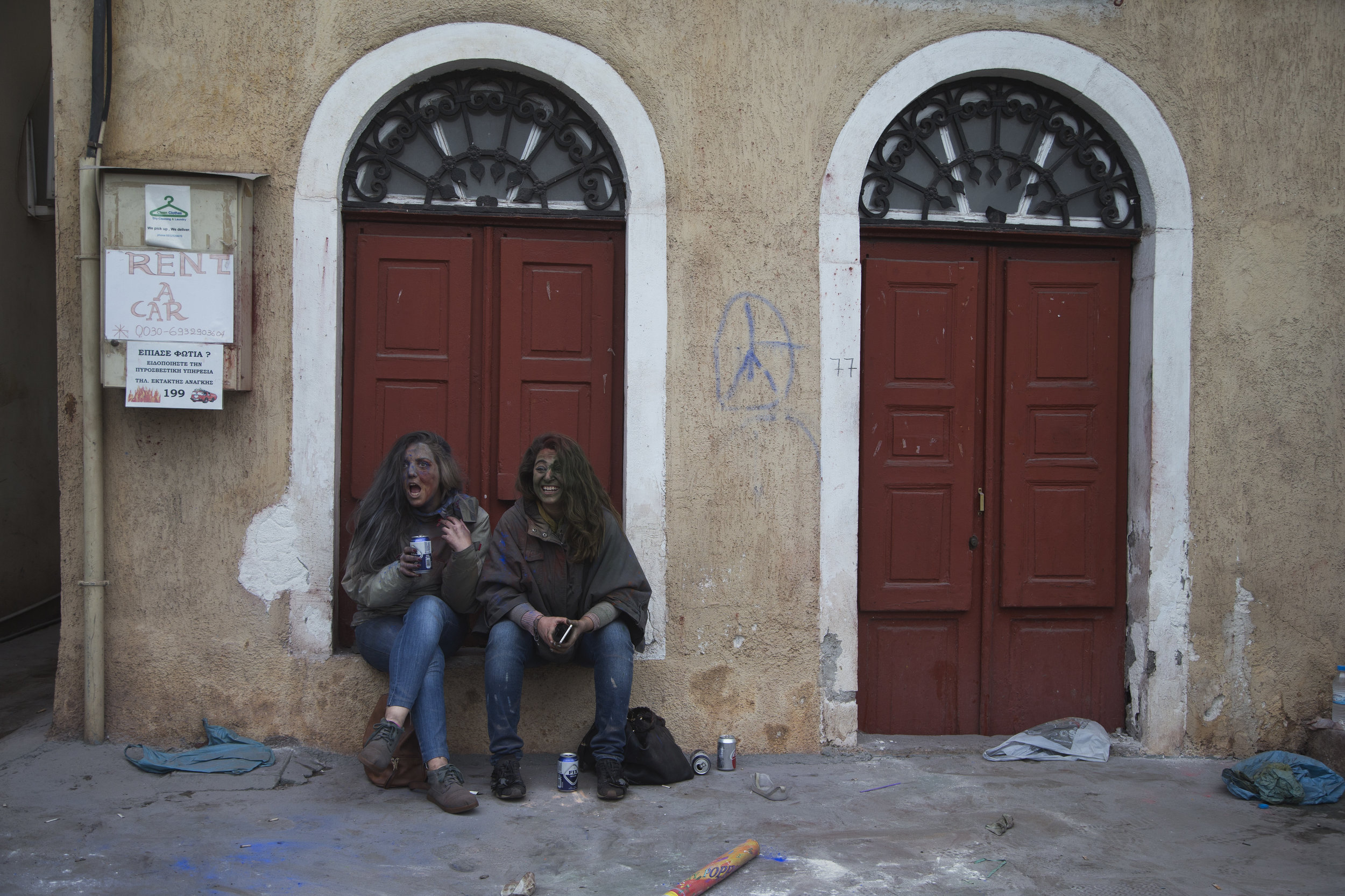 In this Monday, Feb. 19, 2018 photo, twin sisters sit outside a house as they watch revelers taking part in the flour war, a unique colorful flour fight marking the end of the carnival season in the port town of Galaxidi, some 200 kilometers (120 miles) west of Athens.  (AP Photo/Petros Giannakouris)