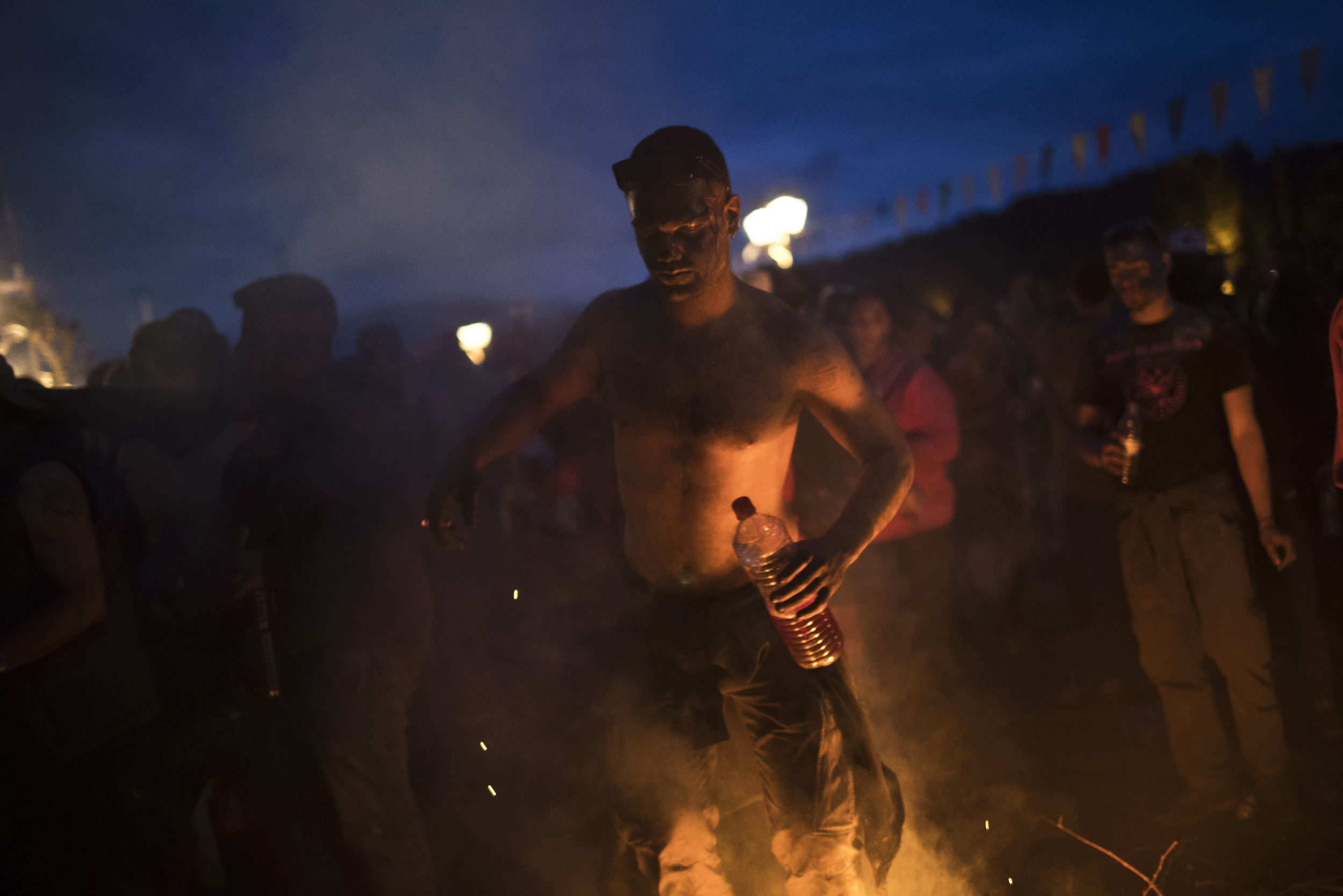 In this Monday, Feb. 19, 2018 photo, a reveler with a bottle of wine dances near a fire during the flour war, a unique colorful flour fight marking the end of the carnival season in the port town of Galaxidi, some 200 kilometers (120 miles) west of Athens.  (AP Photo/Petros Giannakouris)
