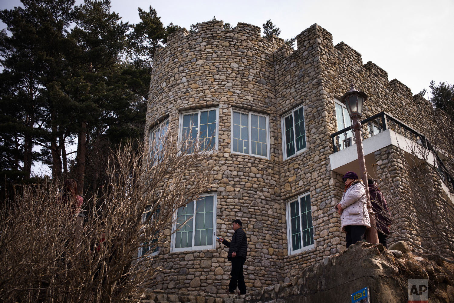 Visitors stand outside the villa known as Hwajinpo Castle, once a holiday home for late North Korea founder Kim Il Sung, at Hwajinpo Beach, South Korea, Monday, Feb. 19, 2018.(AP Photo/Jae C. Hong)