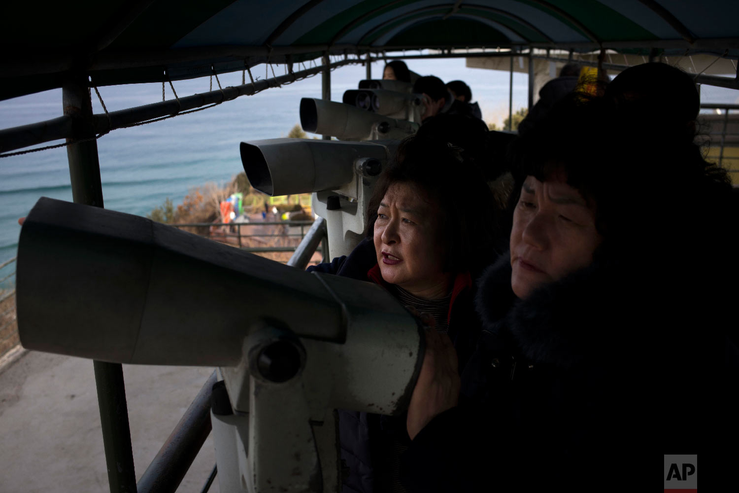 Visitors use binoculars to view North Korea from the Goseong Unification Observatory in Goseong, South Korea, Monday, Feb. 19, 2018. (AP Photo/Jae C. Hong)