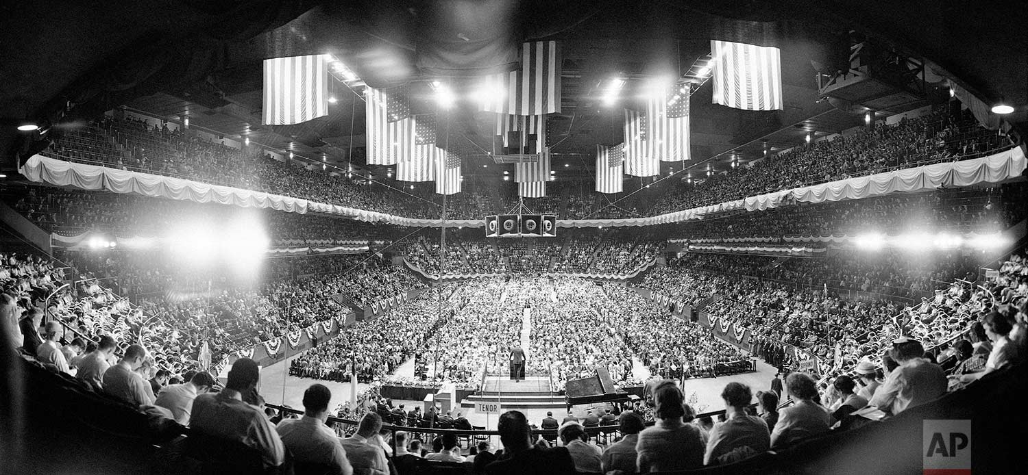 An estimated 13,000 persons sit in Madison Square Garden, New York May 16, 1967 for the second of Evangelist Billy Graham's religious crusade in the city. Beyond the choir singers, foreground, the Baptist preacher addresses assembly from rostrum. (AP Photo/Hans Von Nolde)