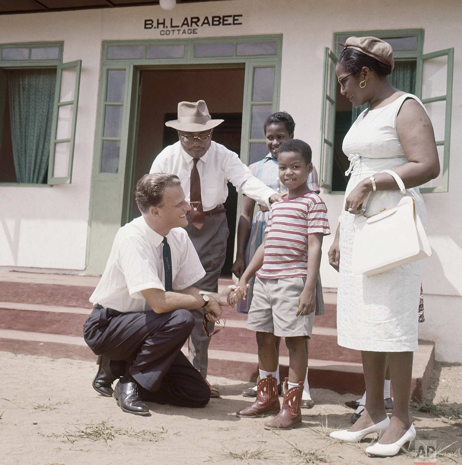 The Rev. Billy Graham, American evangelist, is shown with children at Virginia Village, 20 miles from Montovia in 1960. (AP Photo)