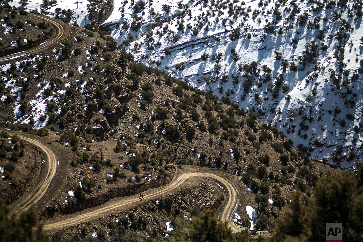 In this Wednesday, Feb. 14, 2018 photo, villagers walk through a slope on their way to Tighanmin, a Middle Atlas village near Azilal, central Morocco. (AP Photo/Mosa'ab Elshamy)