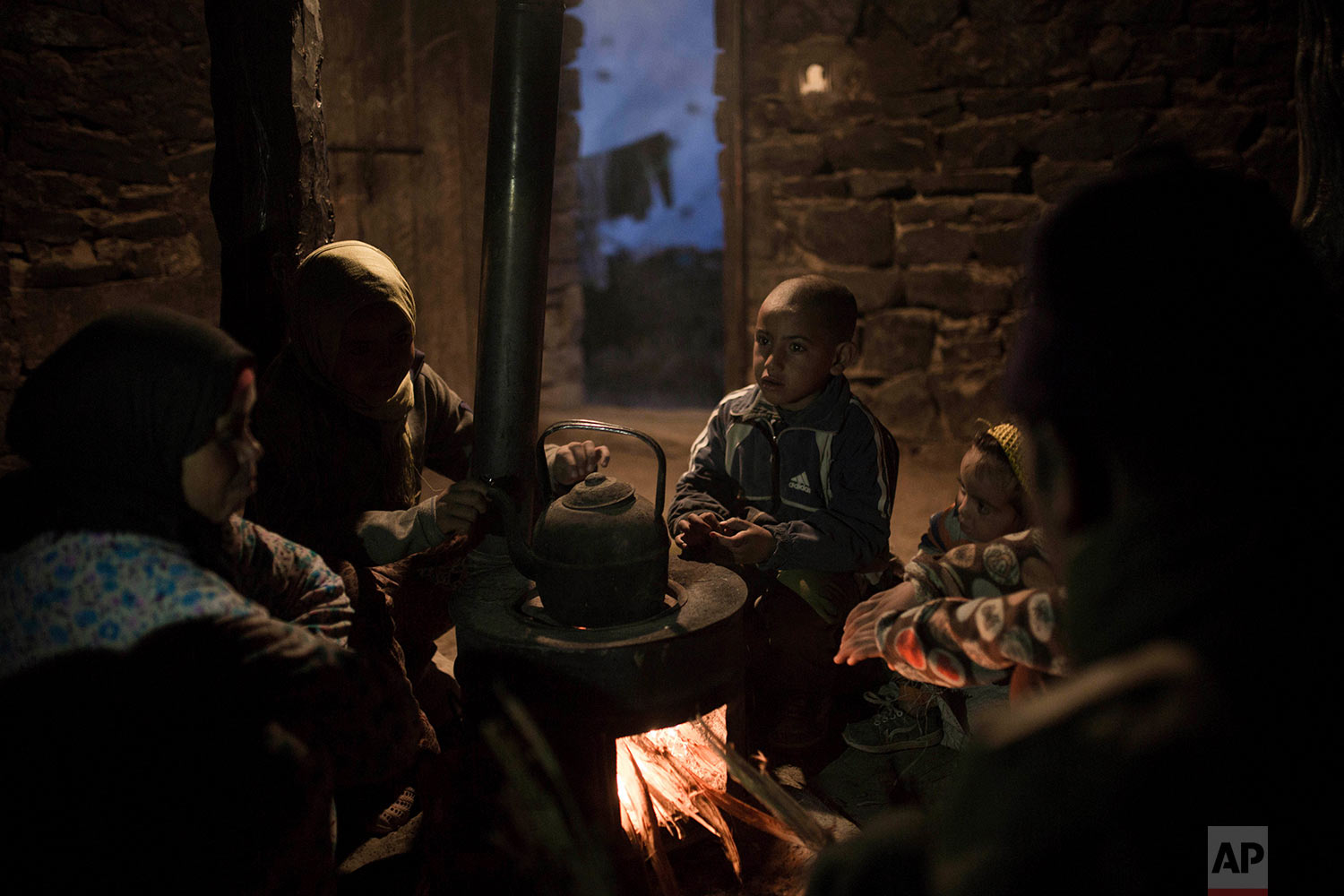 In this Wednesday, Feb. 14, 2018 photo, a family gathers around a fire to warm up inside their home in Tighanmin, a Middle Atlas village near Azilal, central Morocco. (AP Photo/Mosa'ab Elshamy