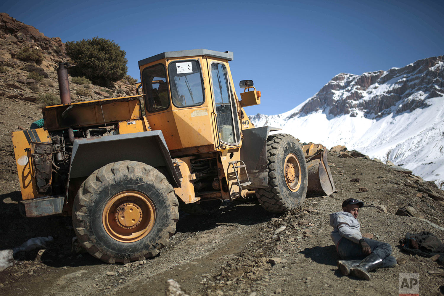 In this Wednesday, Feb. 14, 2018 photo, workers take a rest as they use a vehicle to break through snow near Tighanmin, a Middle Atlas village near Azilal, central Morocco. (AP Photo/Mosa'ab Elshamy)