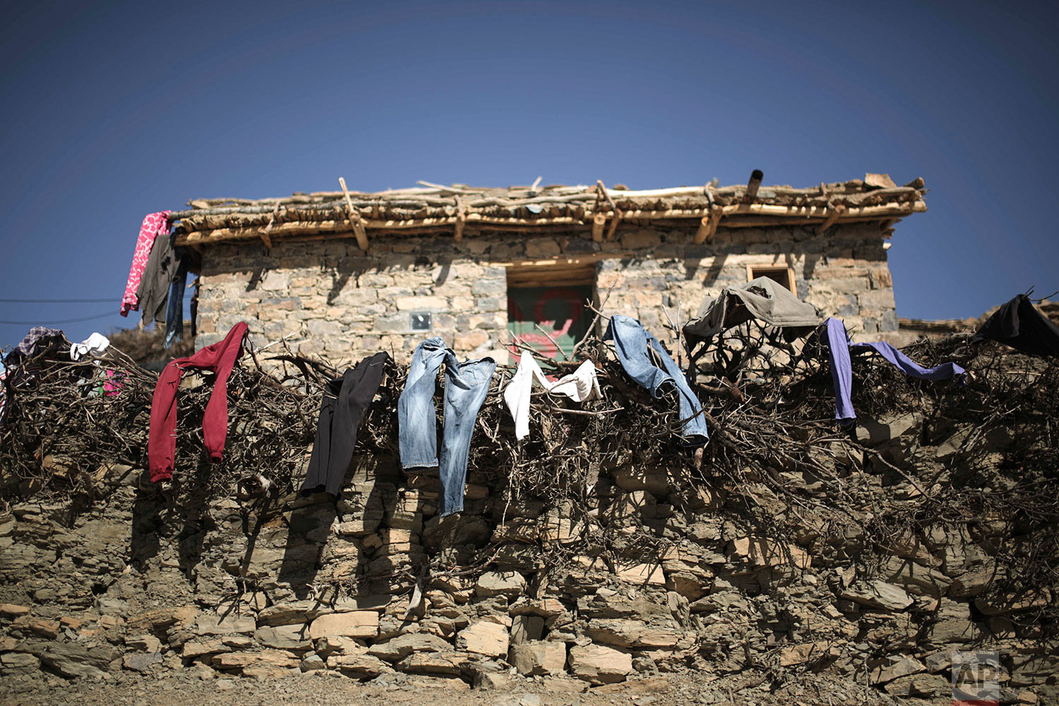In this Wednesday, Feb. 14, 2018 photo, clothes are put out to dry outside a home after heavy snowfall in Tighanmin, a Middle Atlas village near Azilal, central Morocco. (AP Photo/Mosa'ab Elshamy)