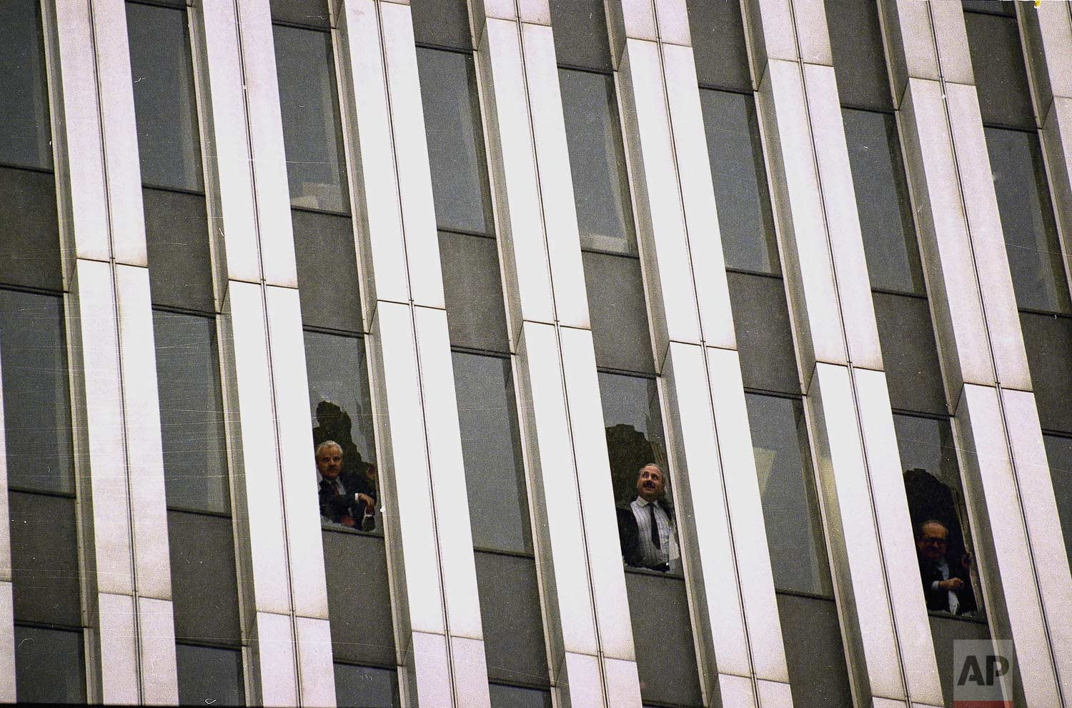 Workers peer through broken windows of the World Trade Center in New York, Feb. 26, 1993, after an explosion in an underground garage rocked the twin towers complex. (AP Photo/Alex Brandon)