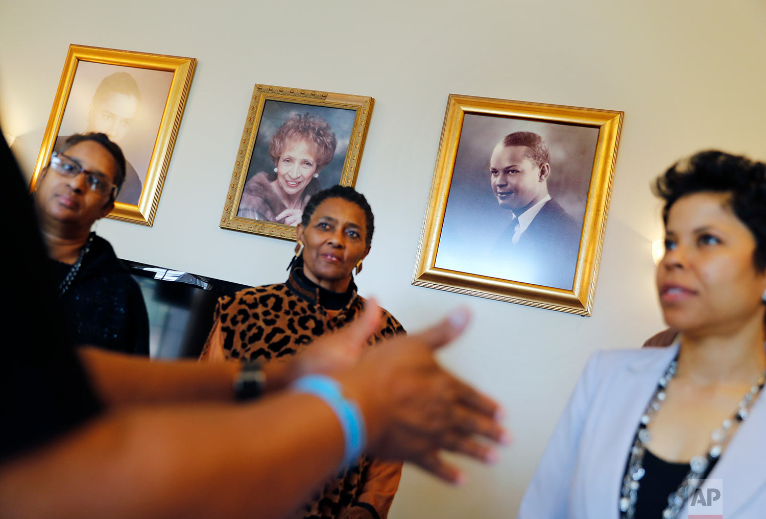 A portrait of Dan Young, who ran the county's only black funeral home that tended to the bodies of the 1946 lynching victims, hangs on the wall of the business now run by his granddaughter Dana Young Levett, right, as she meets with fellow Moore's Ford Movement members Hattie Lawson, center, Kathy Arnold, left, and Tyrone Brooks, in Monroe, Ga., Thursday, Feb. 22, 2018. The group holds an annual march and reenactment of the lynching to raise public awareness that the case remains unsolved. (AP Photo/David Goldman)
