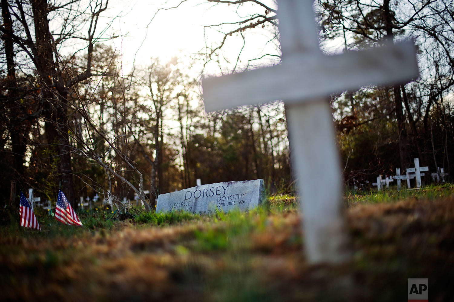 A tombstone marks the grave of George Dorsey and his sister, Dorothy Malcom who in 1946 were stopped by a white mob who dragged them to a riverbank and shot them multiple times, in Bishop, Ga., Thursday, Feb. 22, 2018. (AP Photo/David Goldman)