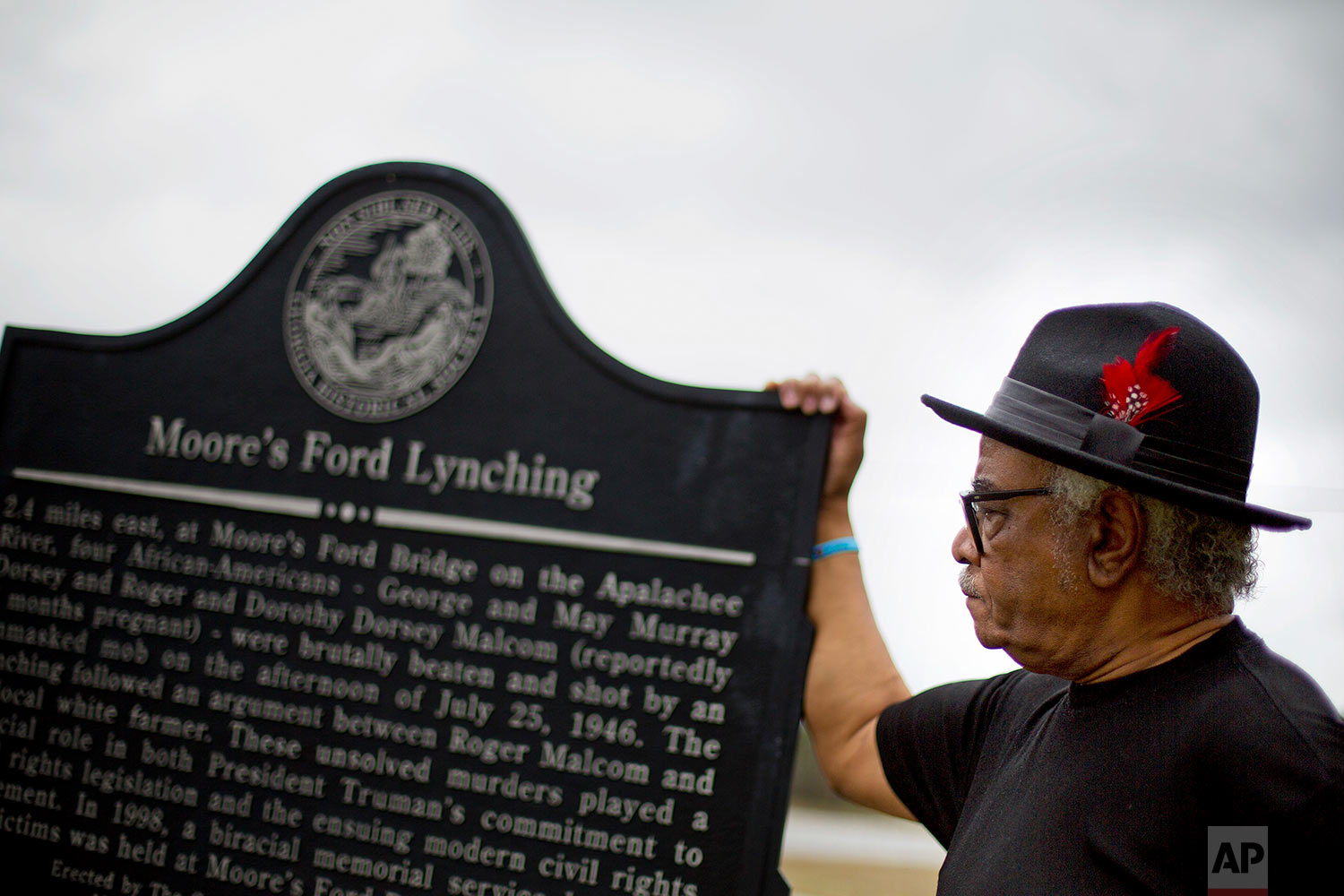 """In this Feb. 22, 2018 photo, Tyrone Brooks, a veteran civil rights activist, stands at a historical marker at the highway turnoff to the rural road where in 1946 two young black couples were stopped by a white mob and shot multiple times in Monroe, Ga. """"We want to perfect the record for history's sake, to make sure this case is never forgotten,"""" said Brooks, who began looking into the lynching in 1968 at the request of the Rev. Martin Luther King Jr. (AP Photo/David Goldman)"""