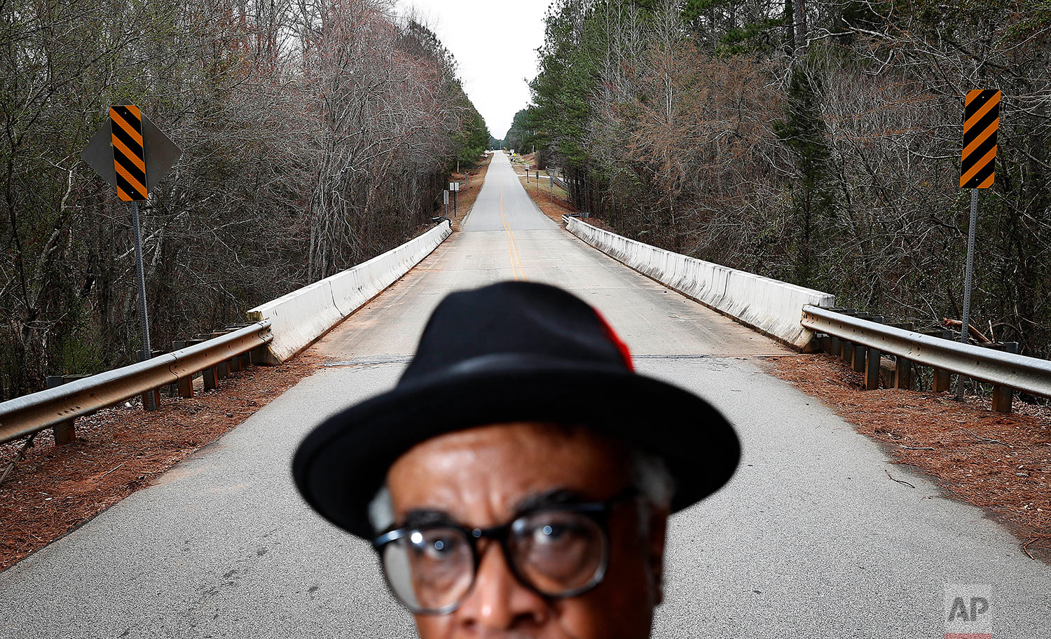 """In this Feb. 22, 2018 photo, Tyrone Brooks, a veteran civil rights activist, stands near the spot along the rural Moore's Ford Road where in 1946 two young black couples were stopped by a white mob and shot multiple times in Monroe, Ga. Even if no one is ultimately prosecuted for the deaths of Roger and Dorothy Malcom and George and Mae Murray Dorsey, it's important to know what happened and who was involved, said Brooks. Nonetheless, he said the closure of the investigations won't stop him. """"Our resolve is as strong as it's ever been,"""" Brooks said. (AP Photo/David Goldman)"""