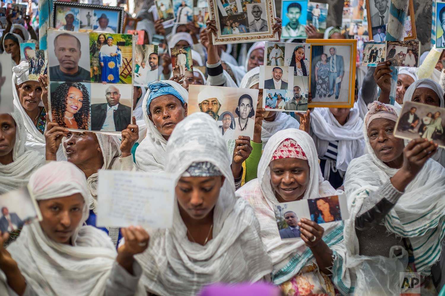 Members of Ethiopia's Jewish community hold pictures of their relatives in Israel, during a solidarity event at the synagogue in Addis Ababa, Ethiopia Wednesday, Feb. 28, 2018. (AP Photo/Mulugeta Ayene)