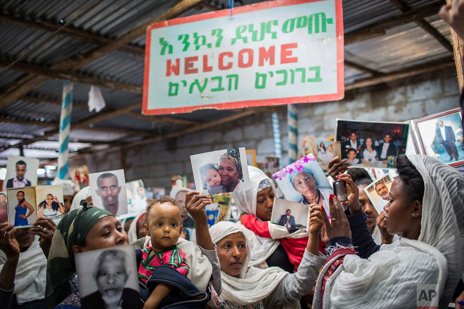 "Members of Ethiopia's Jewish community hold pictures of their relatives in Israel, below a banner reading ""Welcome"" in Amharic, English and Hebrew, during a solidarity event at the synagogue in Addis Ababa, Ethiopia Wednesday, Feb. 28, 2018. (AP Photo/Mulugeta Ayene)"