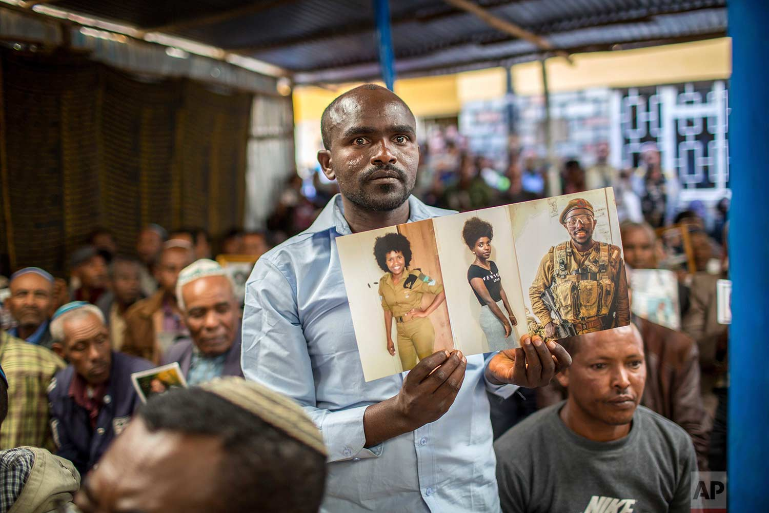 Members of Ethiopia's Jewish community hold pictures of their relatives in Israel during a solidarity event at the synagogue in Addis Ababa, Ethiopia, Wednesday, Feb. 28, 2018. (AP Photo/Mulugeta Ayene)