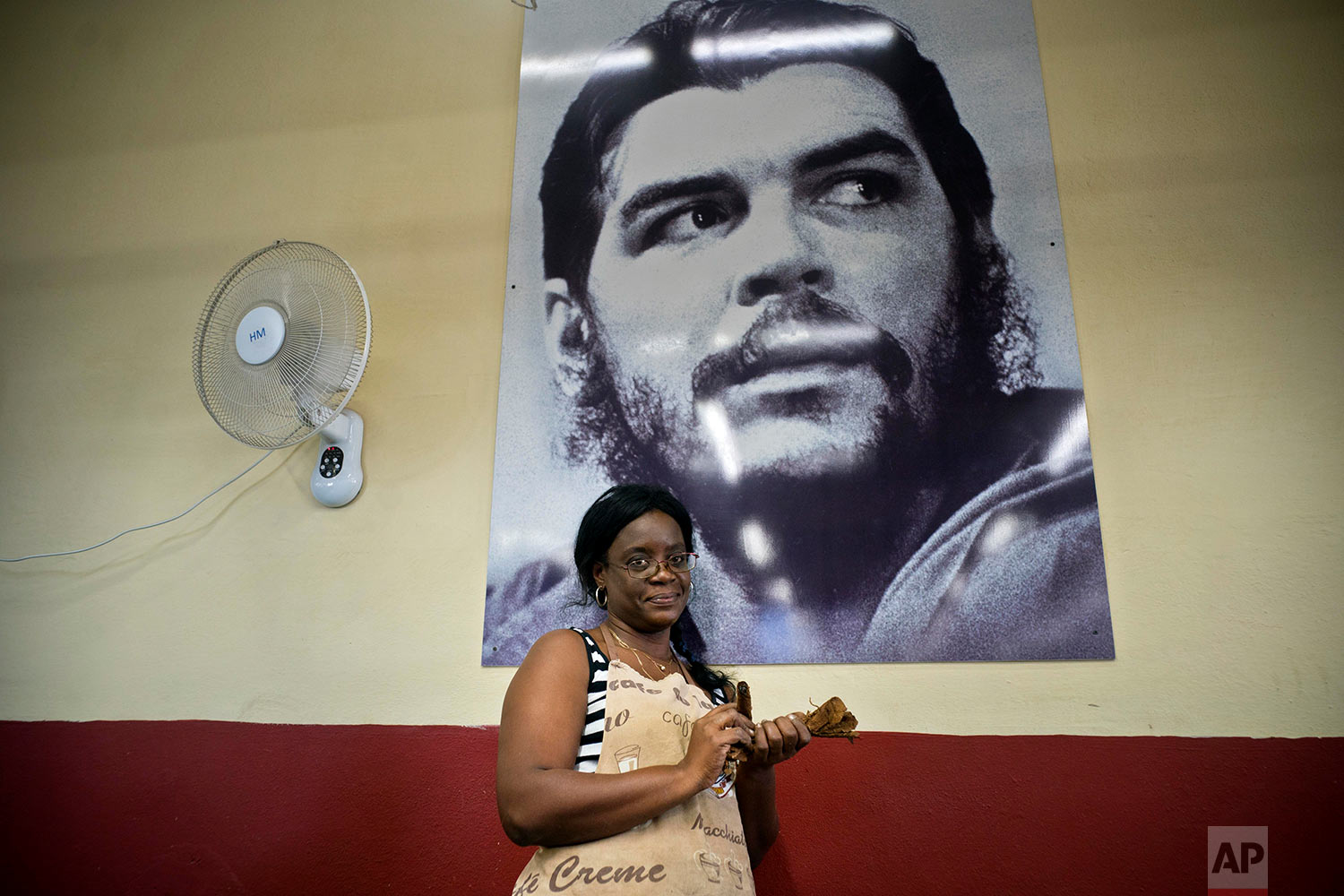 """In this March 1, 2018 photo, Bety Odelys Rios poses in front of a picture of revolutionary hero Ernesto """"Che"""" Guevara, at La Corona cigar factory in Havana, Cuba. (AP Photo/Ramon Espinosa)"""