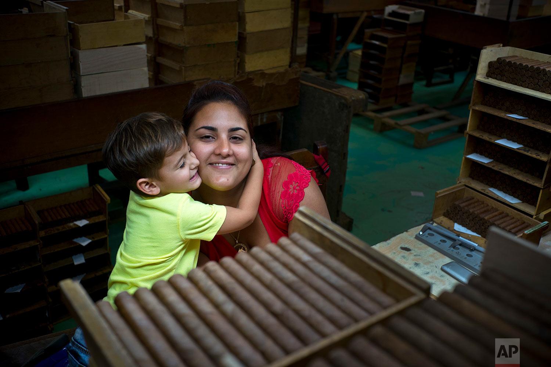 In this March 1, 2018 photo, quality control supervisor Marian Suarez gets a hug from her son Samuel Enrique, at La Corona cigar factory in Havana, Cuba. (AP Photo/Ramon Espinosa)