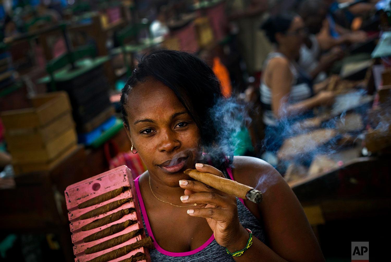 In this March 1, 2018 photo, Yordanka Herrera puffs on a cigar while she poses for a photo at La Corona cigar factory in Havana, Cuba. Herrera works as a cigar roller. (AP Photo/Ramon Espinosa)