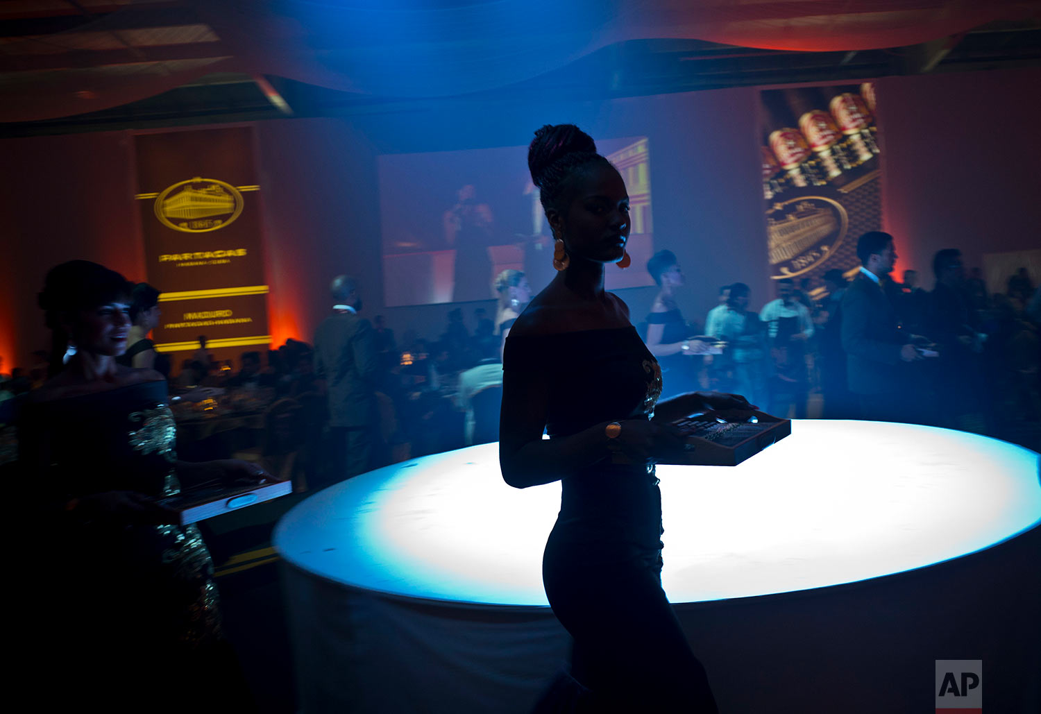 In this March 2, 2018 photo, a model carries a tray of aged cigars for guests, at the gala dinner of the 20th Cigar Festival in Havana, Cuba. (AP Photo/Ramon Espinosa)