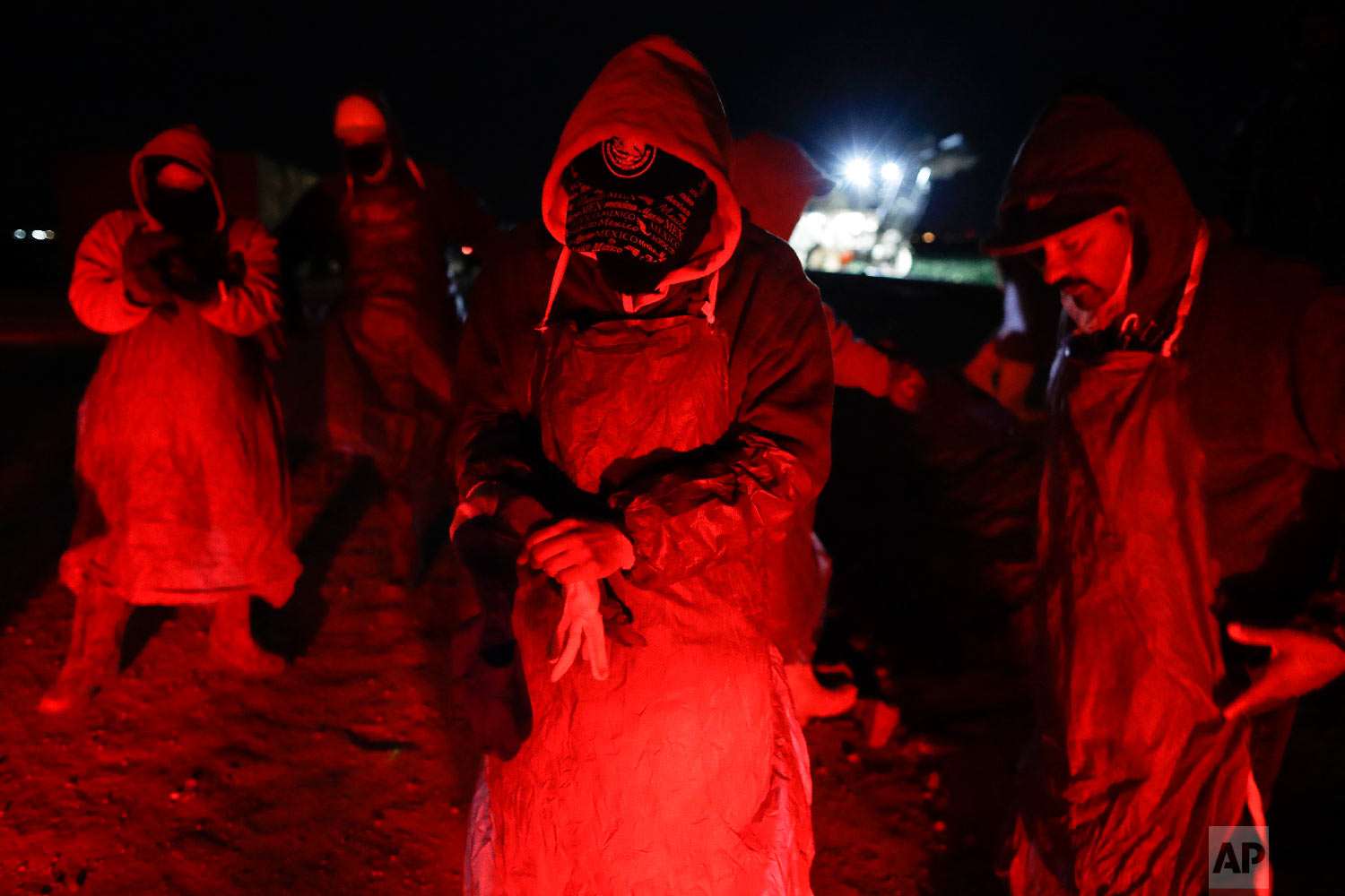 In this March 6, 2018 picture, farmworker Eduardo Garcia, of Mexicali, Mexico, center, puts on an apron and gloves in the glow from the taillights of a bus, as he and his crew arrive at a cabbage field ready for harvest, before dawn outside of Calexico, Calif. (AP Photo/Gregory Bull)
