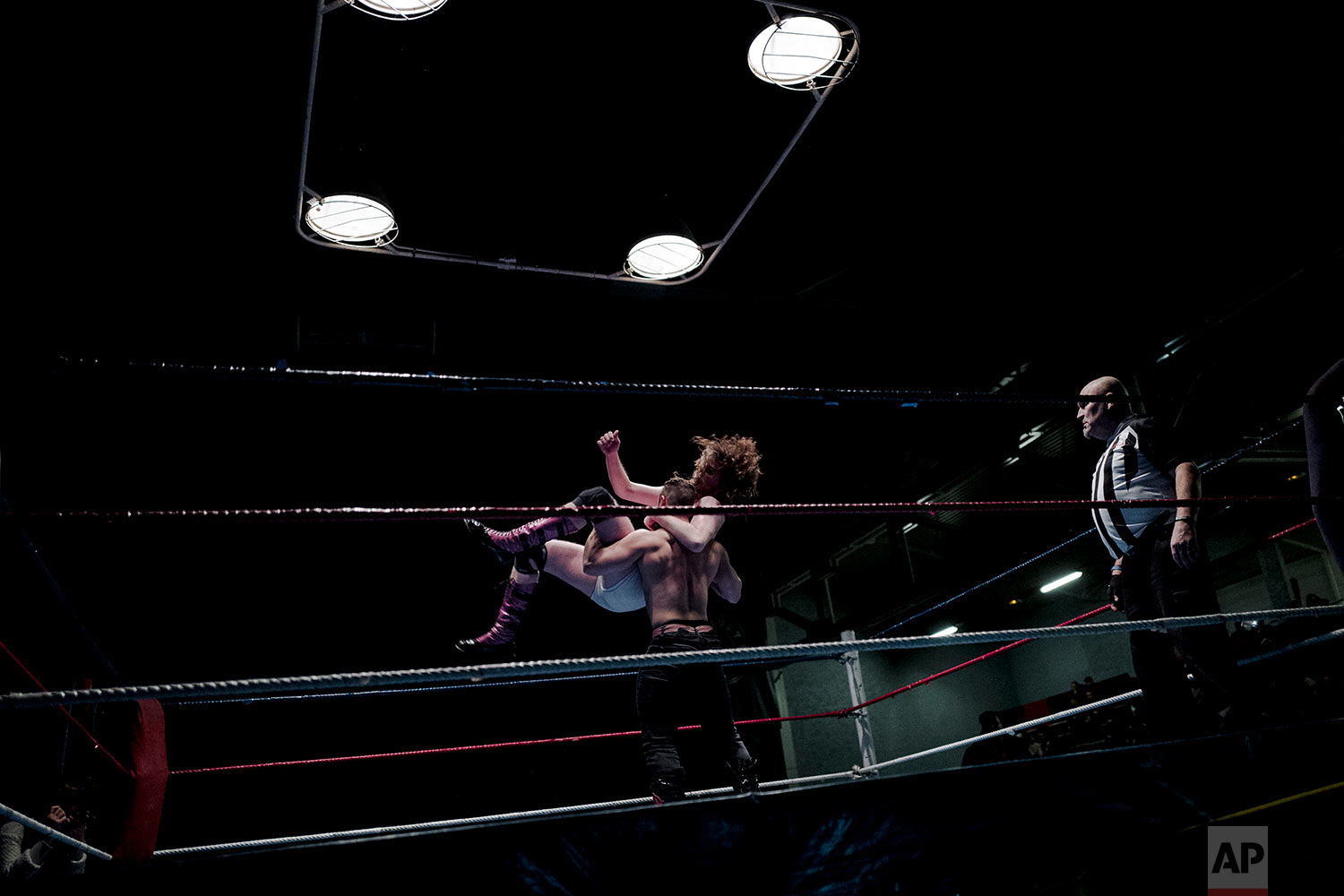 In this photo dated Saturday, Feb. 24, 2018, wrestler Lord Steven Crowley, top, jumps on Zack during a wrestling charity gala in Ivry-sur-Seine, south of Paris, France. (AP Photo/Kamil Zihnioglu)