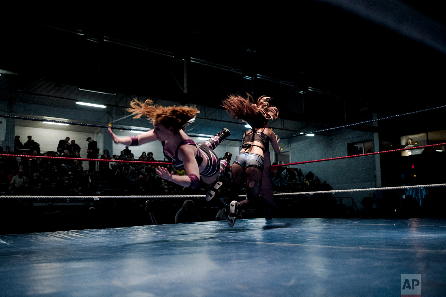 In this photo dated Saturday, Feb. 24, 2018, wrestler Camille, left, fights with Delia during a wrestling charity gala in Ivry-sur-Seine, south of Paris, France. (AP Photo/Kamil Zihnioglu)