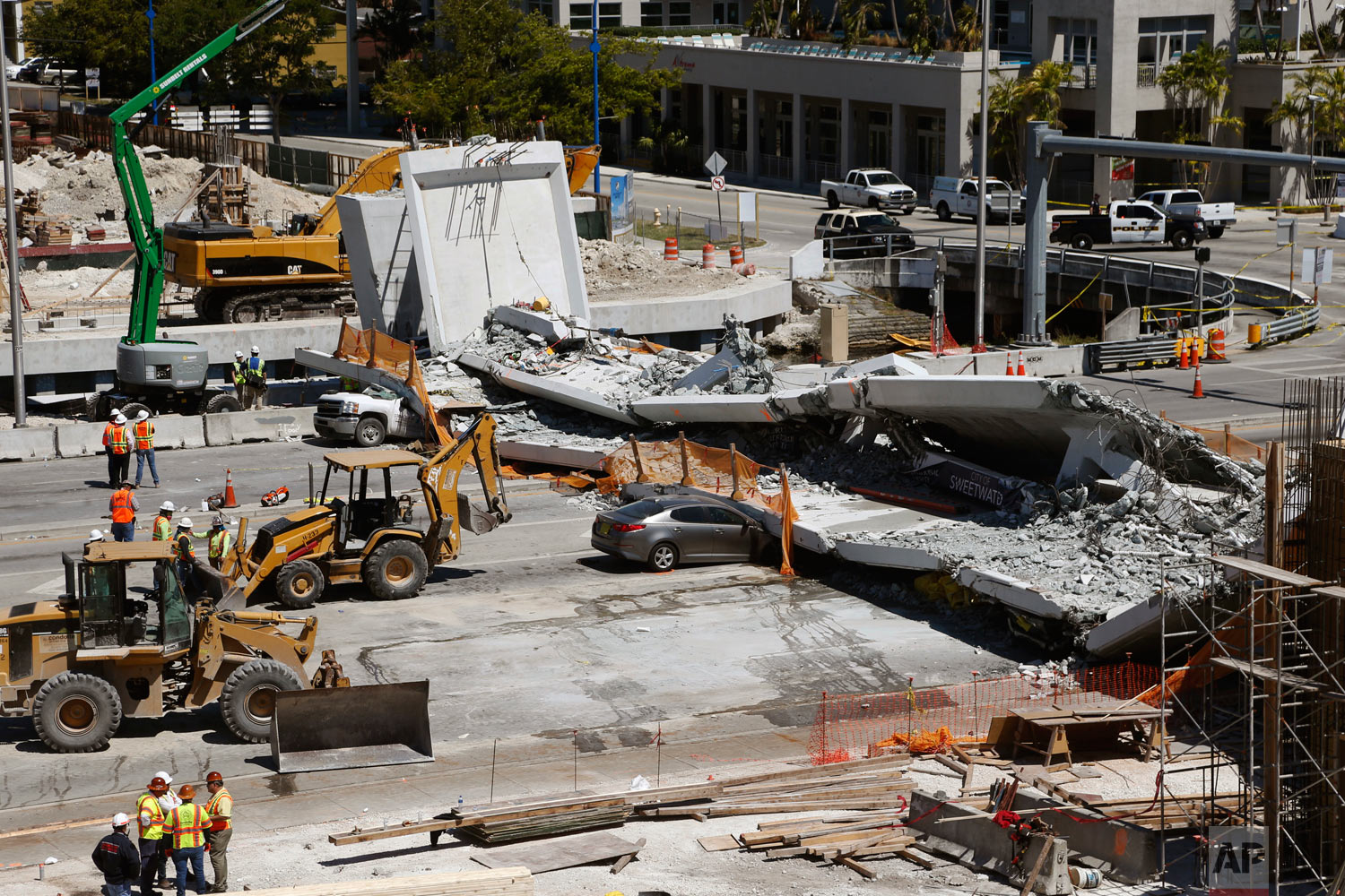 Crushed cars lie under a section of a collapsed pedestrian bridge near Florida International University in the Miami area on Friday, March 16, 2018. The bridge that was under construction collapsed onto a busy highway Thursday afternoon, crushing vehicles beneath massive slabs of concrete and steel, killing and injuring several people, authorities said. (AP Photo/Wilfredo Lee)