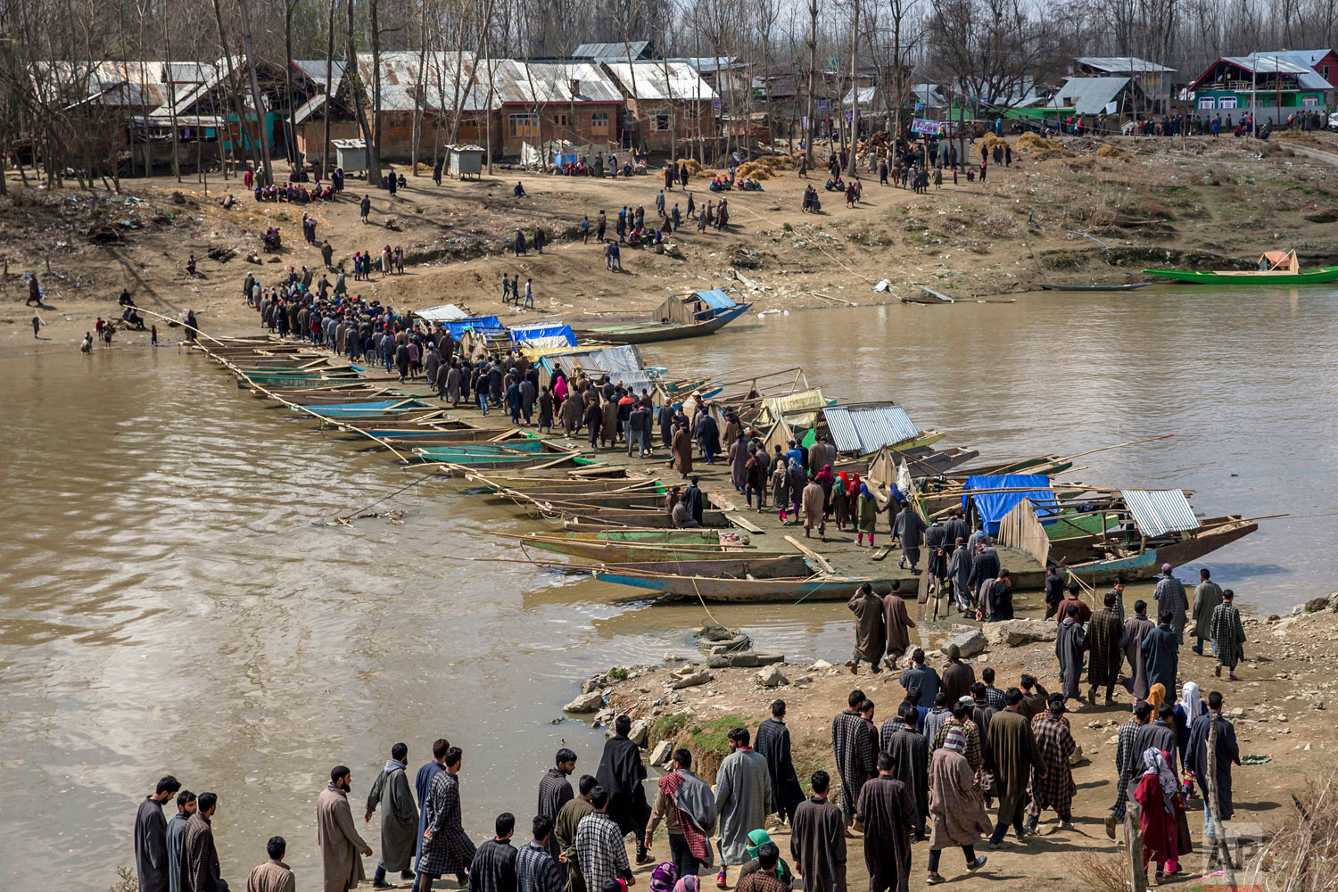 Kashmiri villagers walk on a temporary bridge made by lining up boats forming pathway across the river to attend the funeral of Shabir Ahmad, a suspected rebel, in Awantipora, 30 kilometrers (18 miles) south of Srinagar, Indian-controlled Kashmir, on Friday, March 16, 2018. Rebels have been fighting Indian rule since 1989, demanding Kashmir be made part of Pakistan or become an independent country. India accuses Pakistan of arming and training the rebels, a charge Pakistan denies. (AP Photo/Dar Yasin)