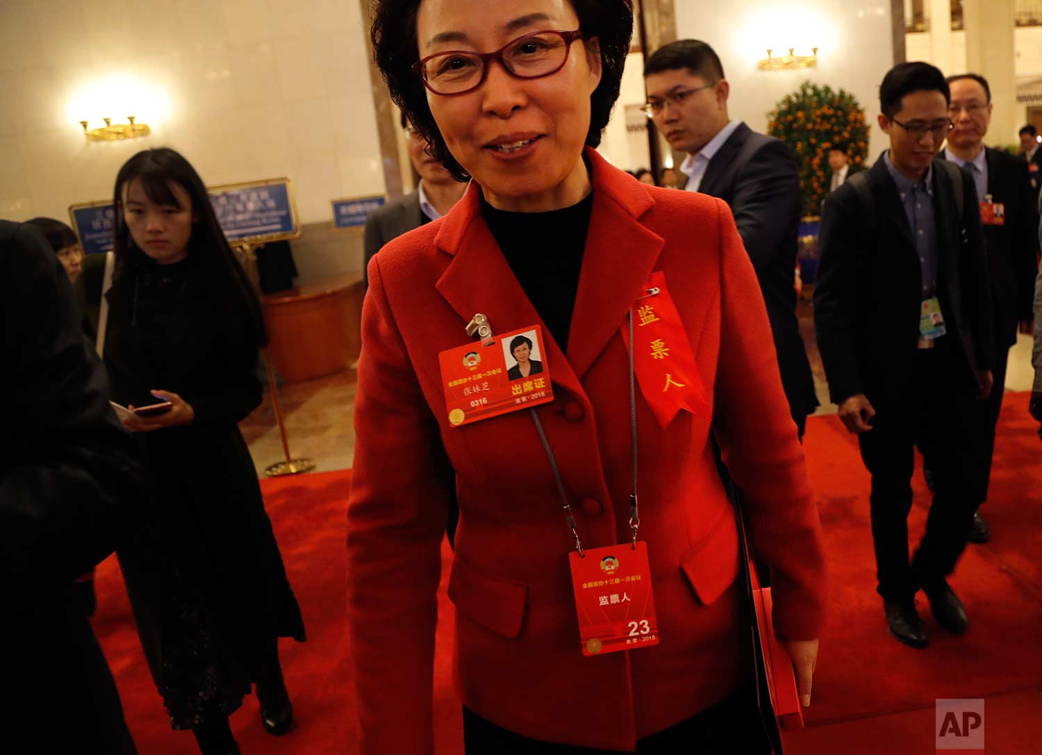 In this Wednesday, March 14, 2018 photo, a delegate in red jacket leaves after attending a plenary session of Chinese People's Political Consultative Conference (CPPCC) at the Great Hall of the People in Beijing. (AP Photo/Aijaz Rahi)