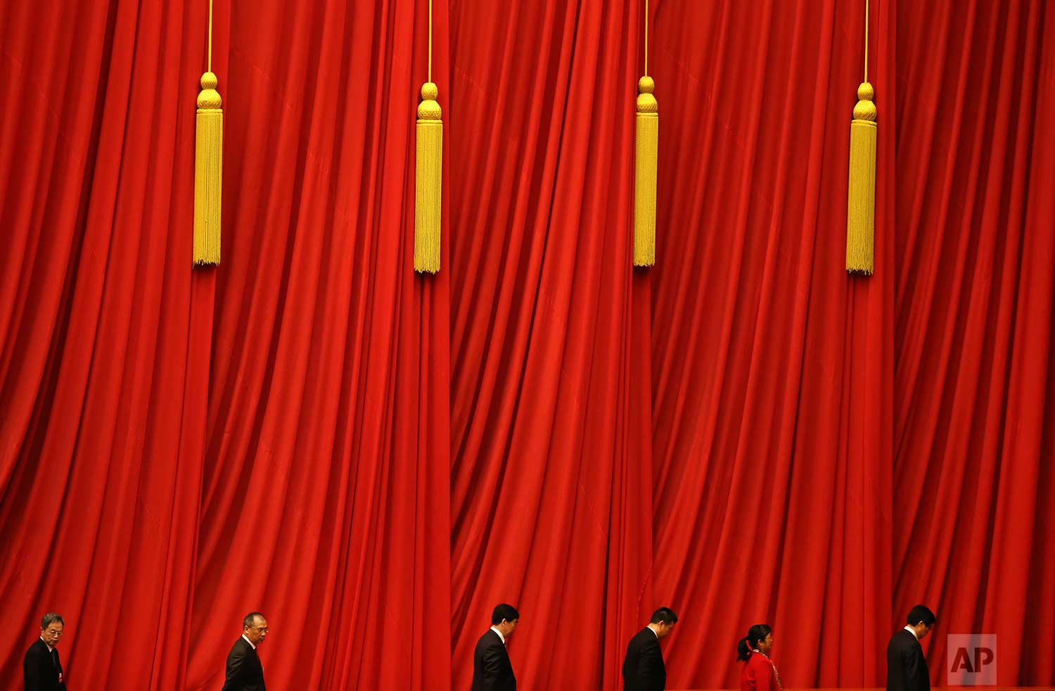 In this Thursday, March 15, 2018 photo, delegates walk past red curtains as they leave after attending the closing session of the Chinese People's Political Consultative Conference (CPPCC) at the Great Hall of the People in Beijing. (AP Photo/Aijaz Rahi)