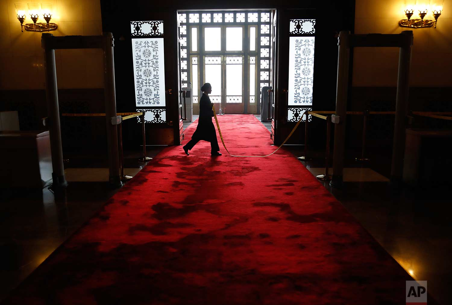In this Tuesday, March 13, 2018 photo, a Chinese security staff walks on a red carpet at the entrance of the Great Hall of Beijing during a provincial group discussion meeting held during China's National People's Congress (NPC) in Beijing. (AP Photo/Aijaz Rahi)