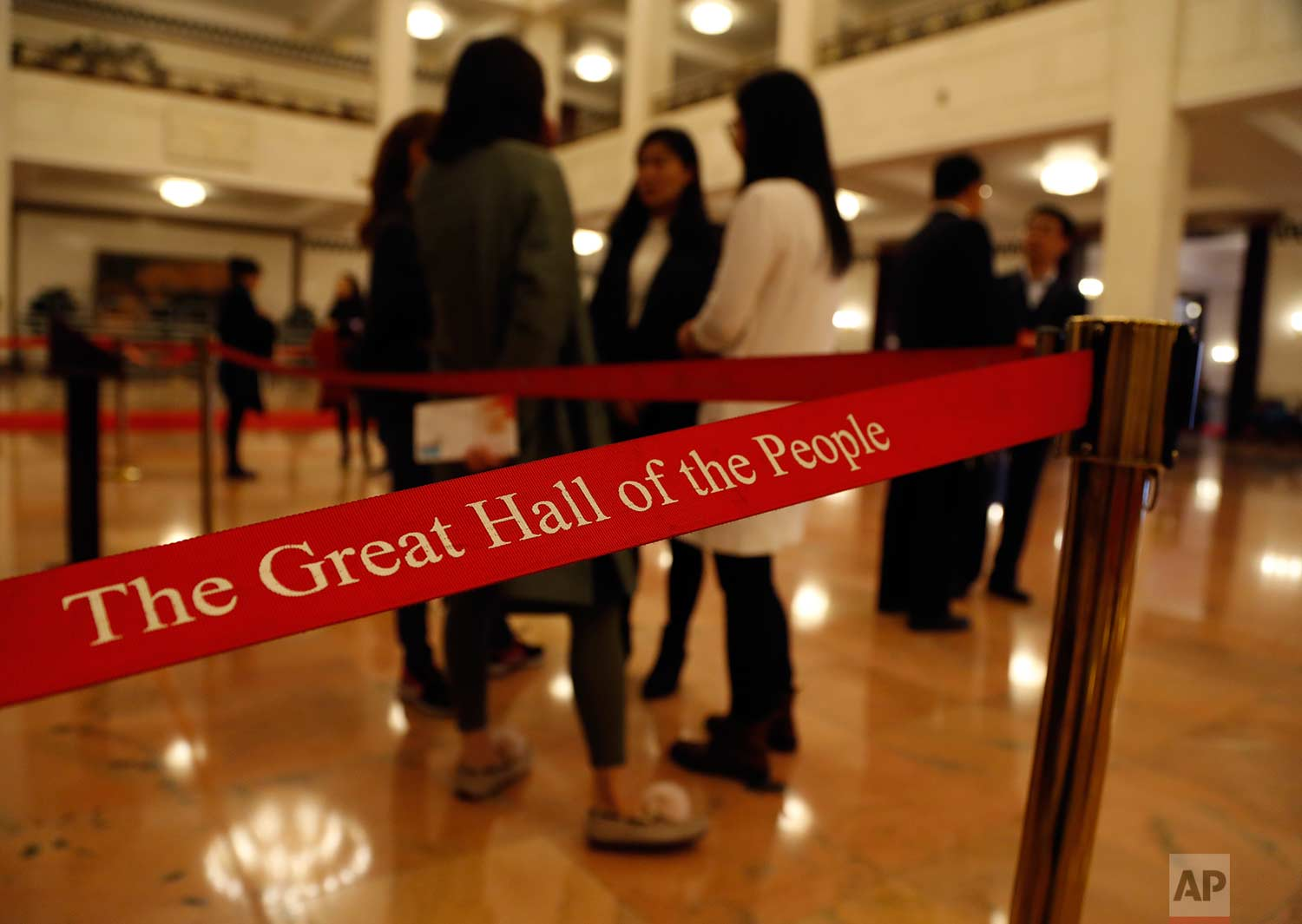 In this Wednesday, March 14, 2018 photo, officials and others stand next to a red rope line that reads 'The Great Hall of China' during a plenary session of Chinese People's Political Consultative Conference (CPPCC) at the Great Hall of the People in Beijing. (AP Photo/Aijaz Rahi)