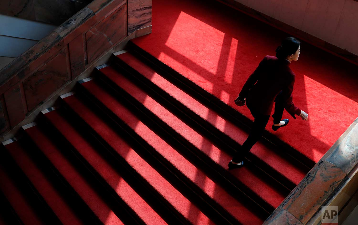 In this Tuesday, March 13, 2018 photo, an attendant climbs stairs covered with red carpet during a plenary session of China's National People's Congress (NPC) at the Great Hall of People in Beijing. (AP Photo/Aijaz Rahi)