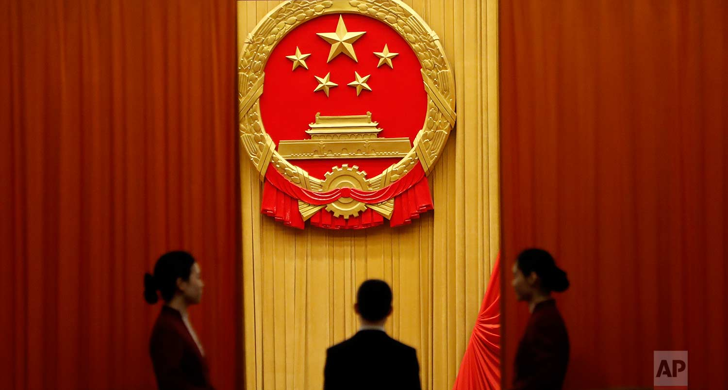 In this Tuesday, March 13, 2018 photo, attendants stand behind curtains below the red and yellow Chinese national emblem before the start of a plenary session of China's National People's Congress (NPC) at the Great Hall of People in Beijing. (AP Photo/Aijaz Rahi)