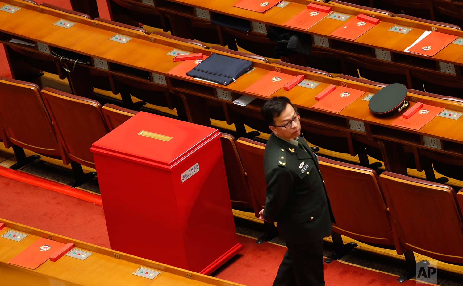 In this Wednesday, March 14, 2018 photo, a military delegate stands next to red ballot box during a plenary session of Chinese People's Political Consultative Conference (CPPCC) at the Great Hall of the People in Beijing, Wednesday, March 14, 2018. (AP Photo/Aijaz Rahi)