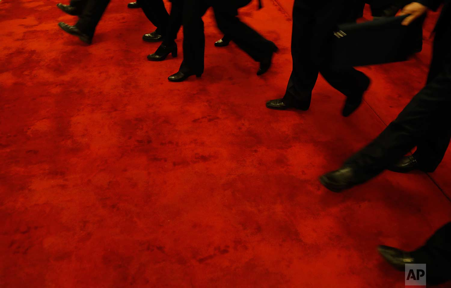 In this Wednesday, March 14, 2018 photo, delegates walk on a red carpet as they leave after attending a plenary session of Chinese People's Political Consultative Conference (CPPCC) at the Great Hall of the People in Beijing. (AP Photo/Aijaz Rahi)