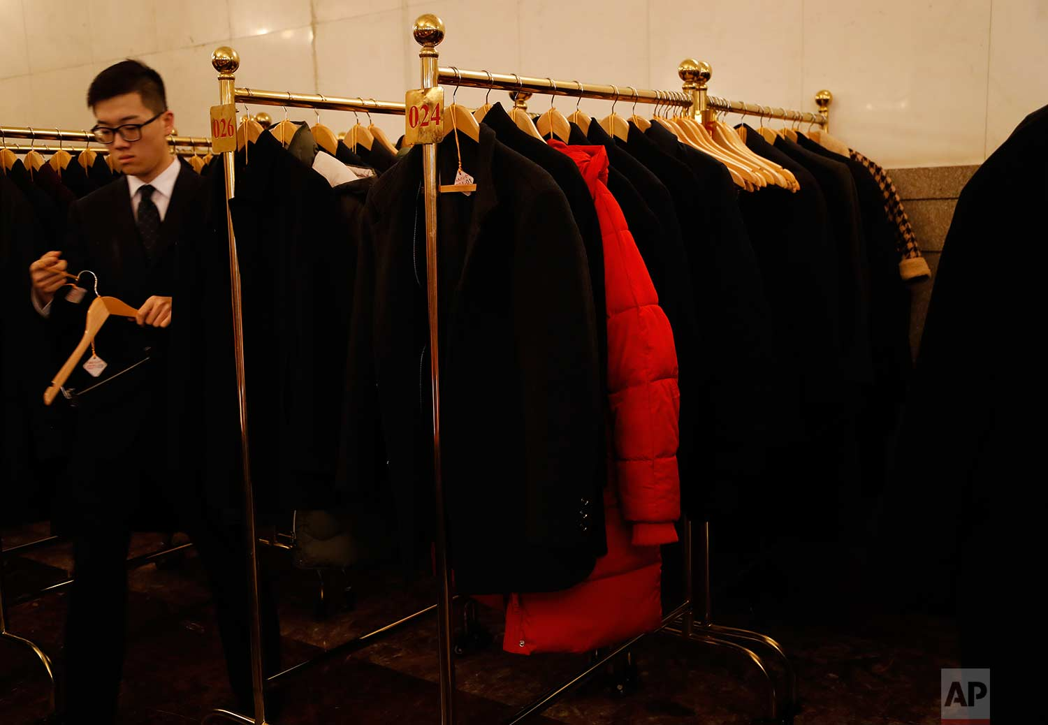 In this Tuesday, March 13, 2018 photo, a red jacket hangs amid black coats before the start during a plenary session of China's National People's Congress (NPC) at the Great Hall of People in Beijing. (AP Photo/Aijaz Rahi)