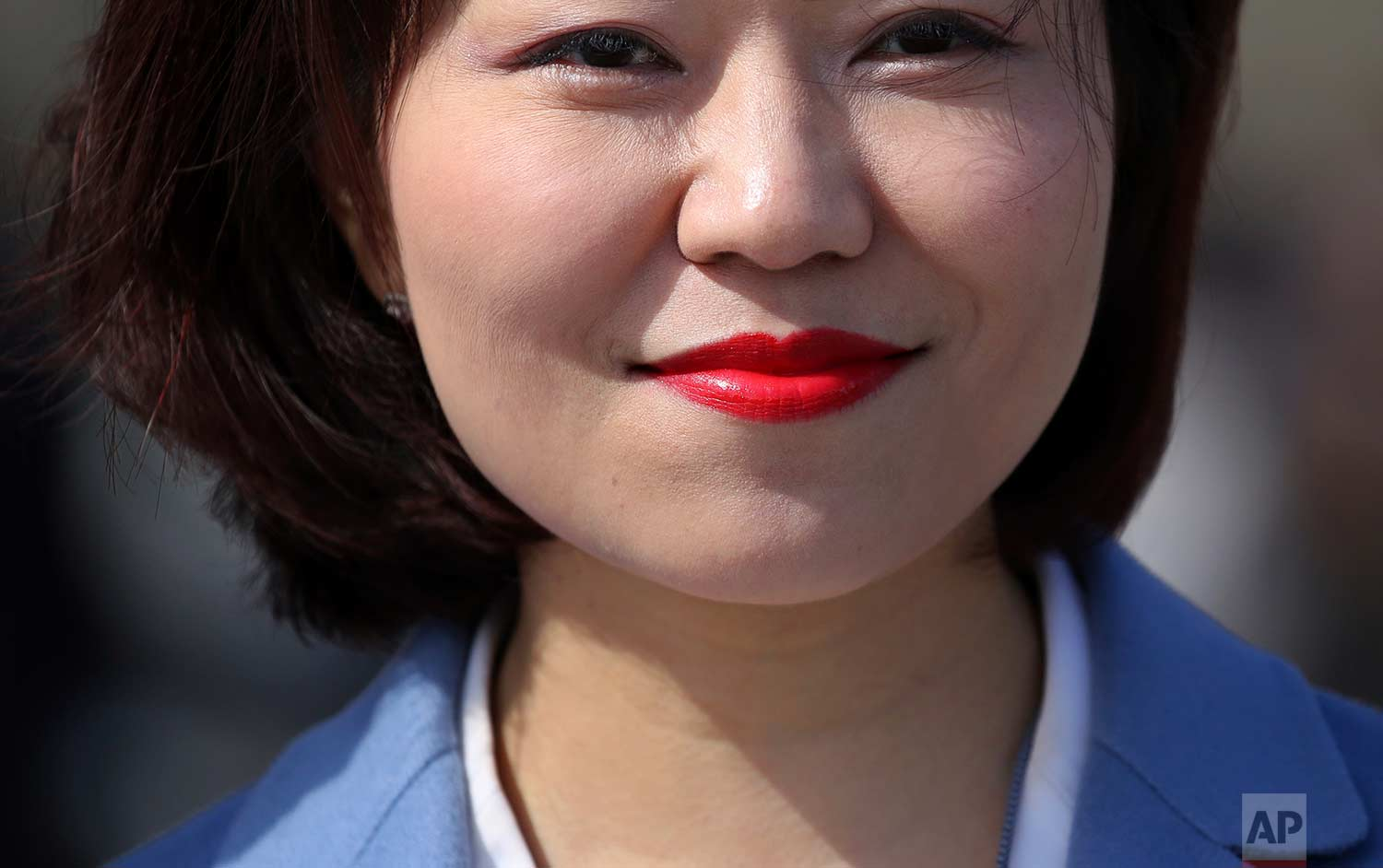 In this Thursday, March 15, 2018 photo, a staff member wears red lipstick as she leaves after the closing session of the Chinese People's Political Consultative Conference (CPPCC) at the Great Hall of the People in Beijing. (AP Photo/Aijaz Rahi)