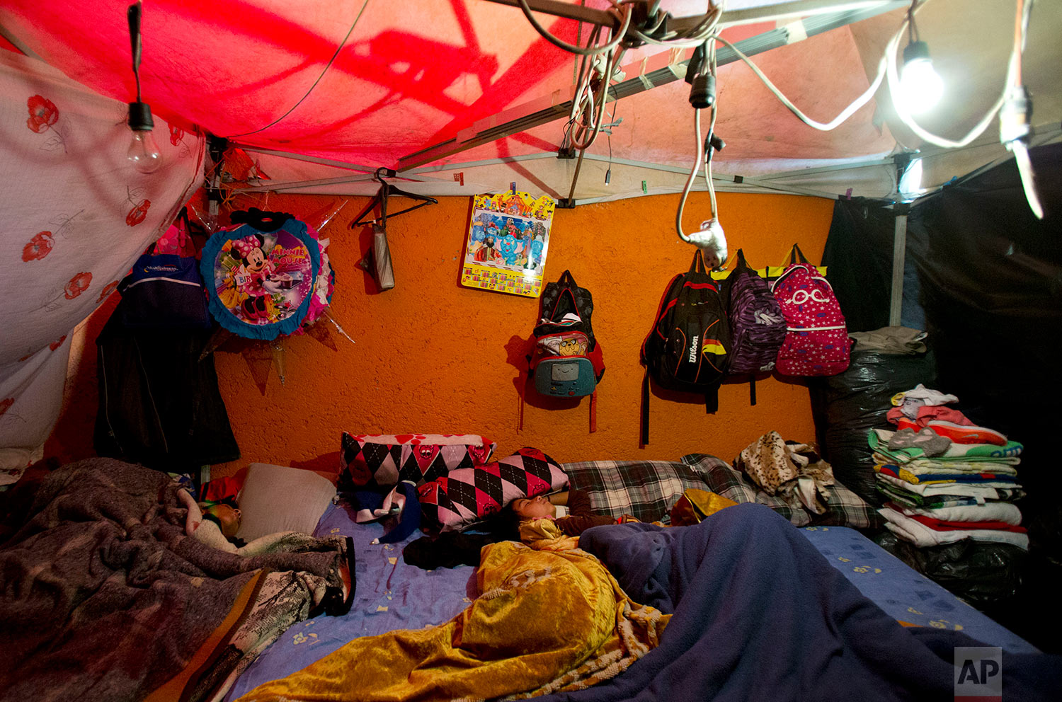 Children sleep in a shelter built against the external wall of a house, at a tent camp outside earthquake-damaged Independencia 18 in Mexico City, Jan. 5, 2018. (AP Photo/Rebecca Blackwell)