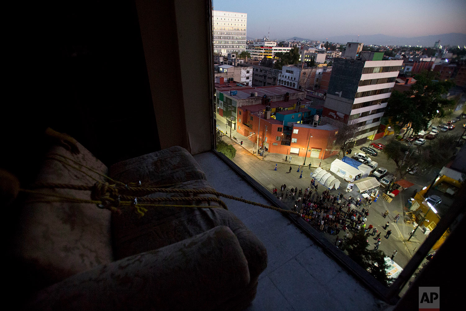 """Movers prepare to lower a couch out through the missing windows of an apartment inside the condemned """"Great Bear"""" building, the first within the complex to be demolished after the 2017 earthquake, in the Doctores neighborhood of Mexico City, Jan. 11, 2018.(AP Photo/Rebecca Blackwell)"""