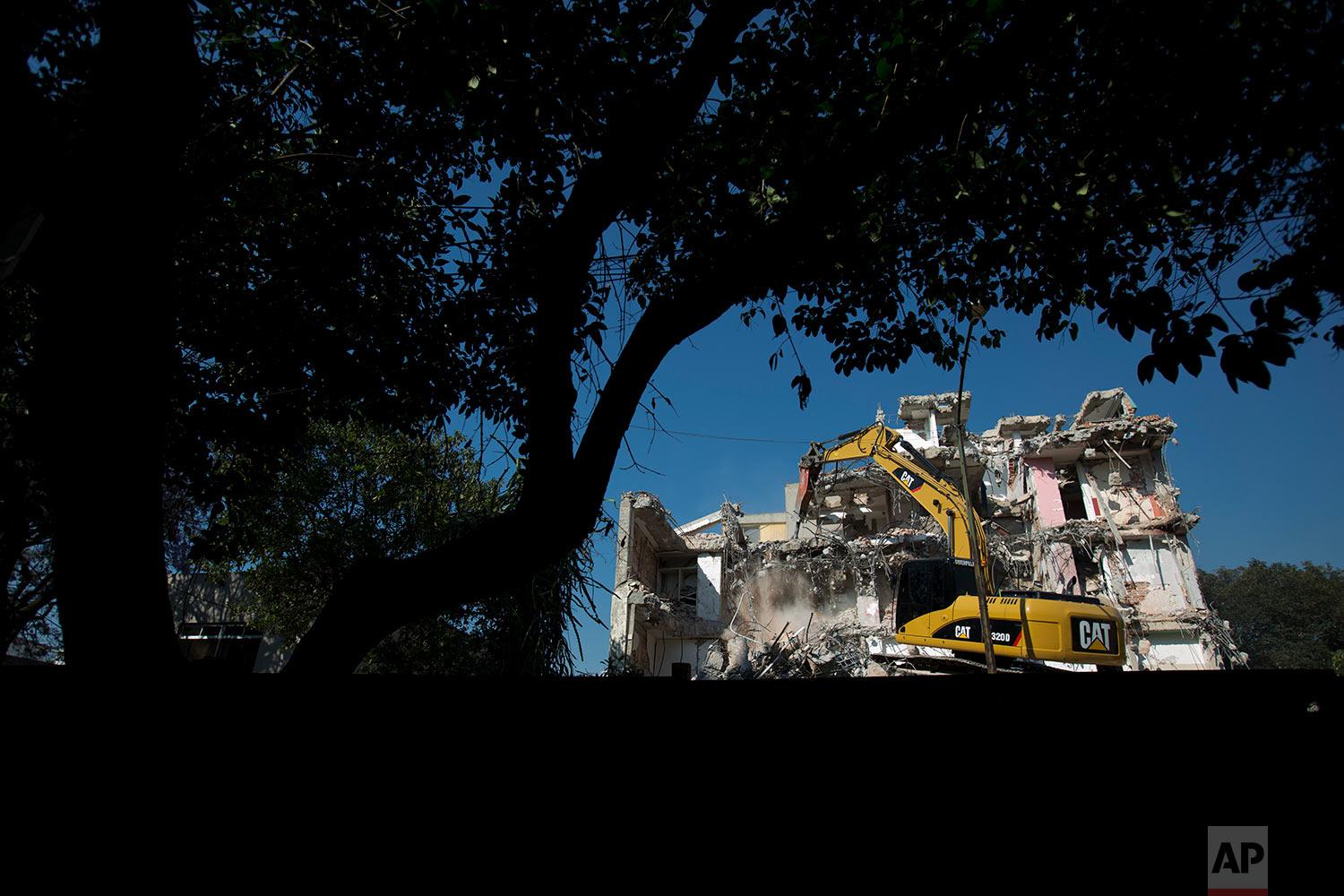 In this March 16, 2018 photo, an eight-story apartment building is demolished at Toluca 43 in the Roma Sur neighborhood of Mexico City. (AP Photo/Rebecca Blackwell)