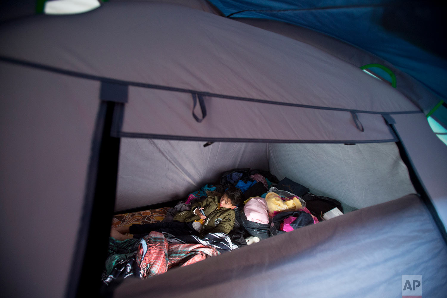 In this March 13, 2018 photo, 7-year-old Kaled Haebran Rivera watches videos on a cell phone inside the tent where he lives with his family outside earthquake-damaged Independencia 18 in Mexico City. (AP Photo/Rebecca Blackwell)