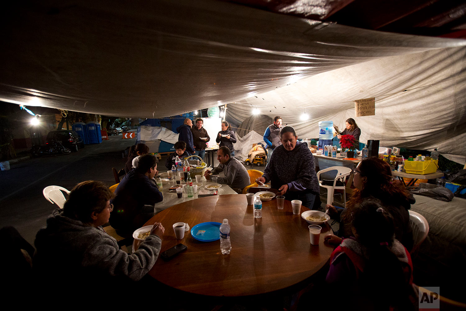 """In this Jan. 12, 2018 photo, residents of an earthquake-damaged apartment building at 5 de Febrero and Guipuzcoa gather for a hot dinner brought by volunteers from the earthquake relief group """"Ayudame Hoy,"""" in the tent camp where they have been living outside their building in Mexico City. (AP Photo/Rebecca Blackwell)"""