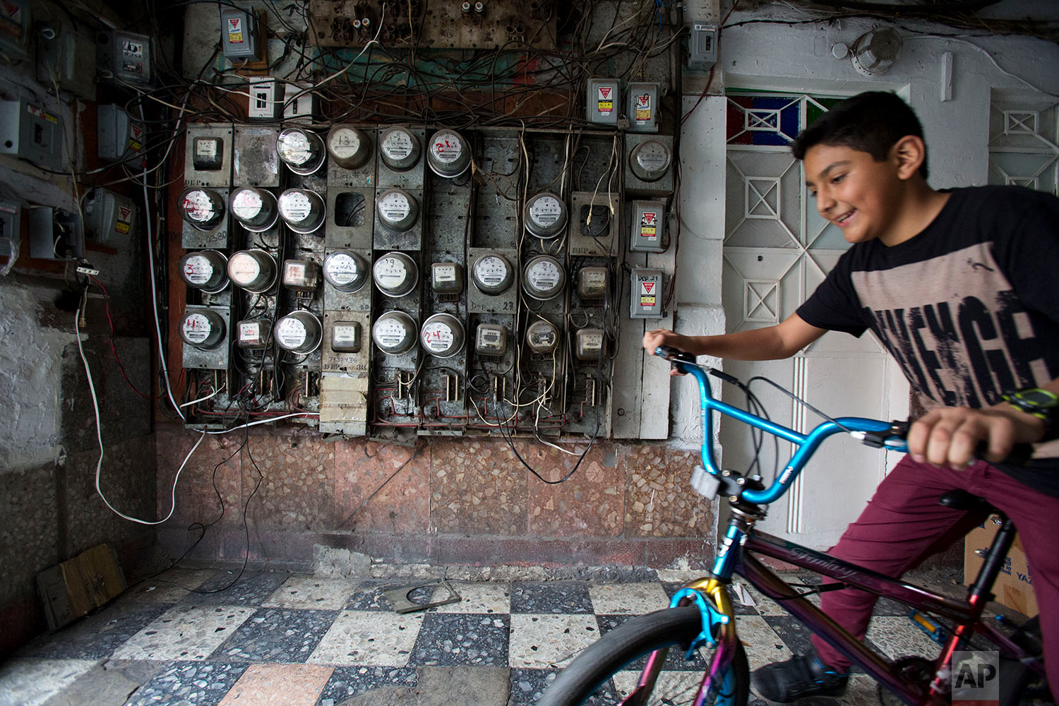 In this Jan. 5, 2018 photo, a boy living with his family in a tent camp in the street quickly fetches his bike from inside the earthquake-damaged building at Independencia 18 in Mexico City. (AP Photo/Rebecca Blackwell)
